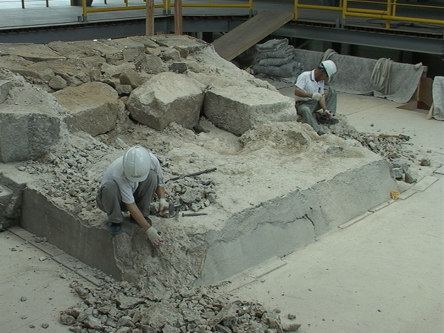 Stonemasons dismantle concrete from the original stone blocks. (Cultural Heritage Administration)