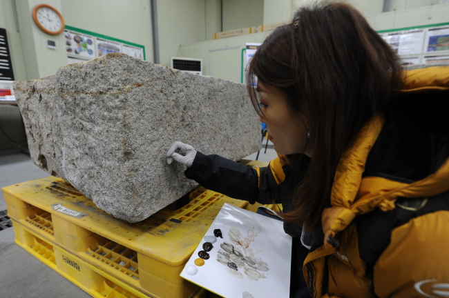 A staff member colors the new stone block to achieve a balanced shade with old stone blocks. (Cultural Heritage Administration)