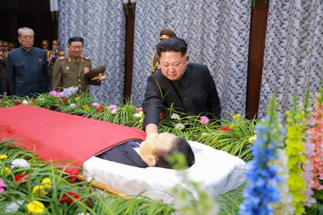 A handout picture provided by North Korea`s state-run Rodong Sinmun newspaper on 31 December 2015 shows North Korean leader Kim Jong-un, touching the body of Kim Yang-gon, a secretary of the ruling Workers` Party of Korea and one of his key aides handling inter-Korean affairs, as he visits the mortuary of Kim to pay homage in Pyongyang, North Korea, 30 December 2015. Kim, one of the two ranking North Korean officials who attended the rare inter-Korean high-level talks in August, died in a car accident on 29 December. (Yonhap/Rodong Sinmun)