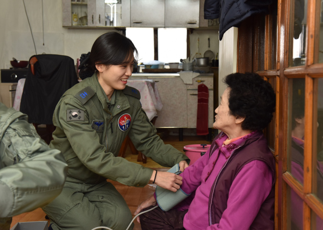 An elderly Korean woman (right) is receiving medical care from a military nurse. Yonhap