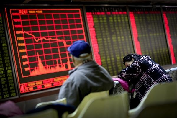 A woman takes a nap as a man looks at an electronic board displaying stock prices at a brokerage house in Beijing, Monday, Jan. 4. (AP-Yonhap)
