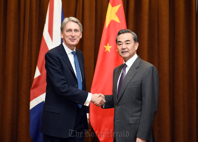 Chinese Foreign Minister Wang Yi (right) shakes hands with British Foreign Secretary Philip Hammond in Beijing on Tuesday. (Xinhua-Yonhap)