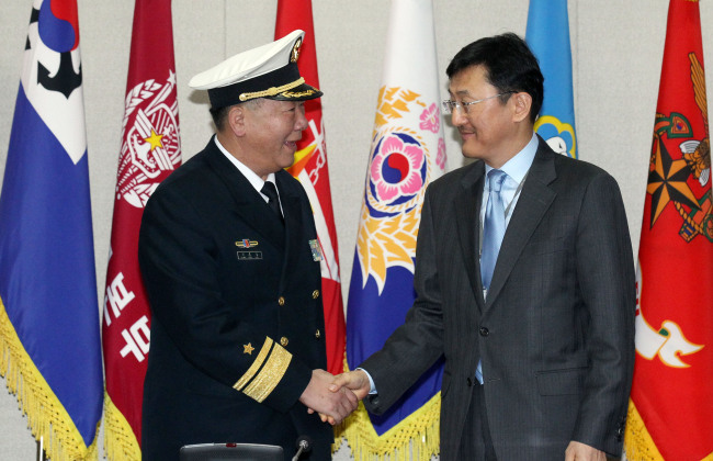 Yoon Soon-gu (right), director general of the international policy bureau at Seoul's Defense Ministry, shakes hands with his Chinese counterpart Guan Youfei on Friday.(Yonhap)