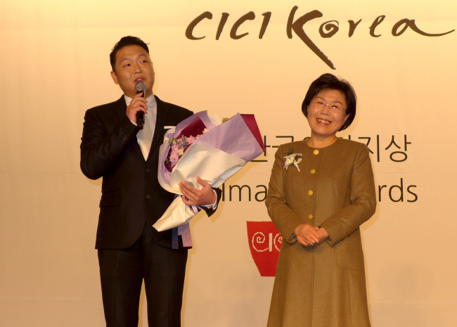 Korean singer Psy (left) accepts the Korea Image Stepping Stone Award from Choi Jung-wha, president of the Corea Image Communications Institute, at the annual award ceremony reception at Intercontinental Seoul Coex on Tuesday. (Joel Lee/The Korea Herald)