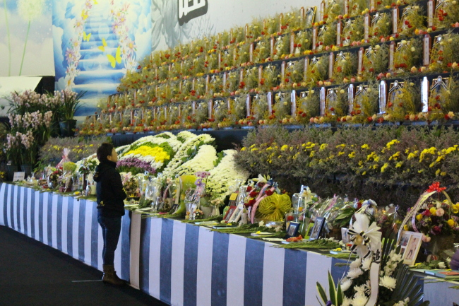 The mother of a Danwon High School student who lost his life in the Sewol accident weeps in front of her son's photo at a joint memorial in Ansan, Gyeonggi Province. (Yoon Min-sik/The Korea Herald)