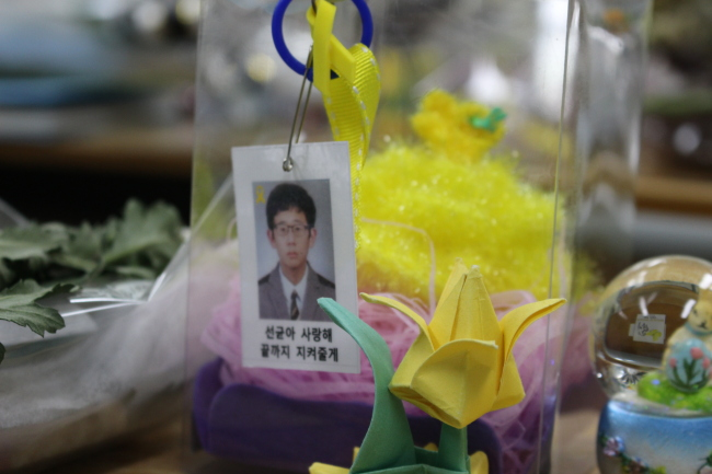 """A photo of a student victim is hung on a box of gifts left at his desk. Below the photo is the message """"Seongyun, I love you. I'll protect you to the end."""" (Yoon Min-sik/The Korea Herald)"""
