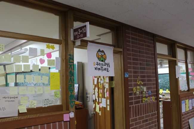 """A sign on the door of one of the Memory Classrooms with the message, """"Please protect our classrooms."""" (Yoon Min-sik/The Korea Herald)"""
