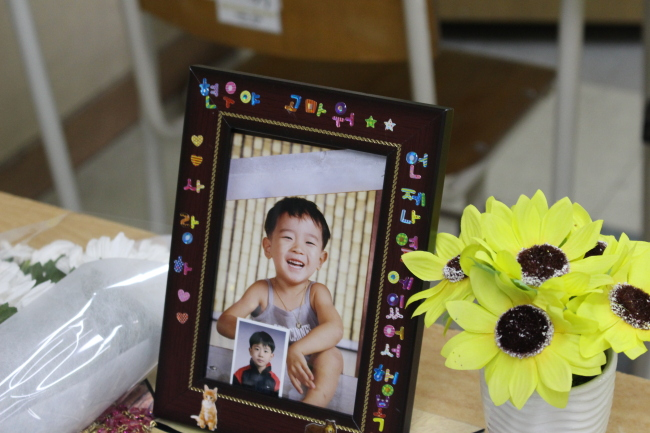 """A childhood photo of Jeon Hyeon-woo is laid on his desk. The messages on the frame reads, """"Hyeon-woo, I love you. Thank you for always being with me."""" (Yoon Min-sik/The Korea Herald)"""