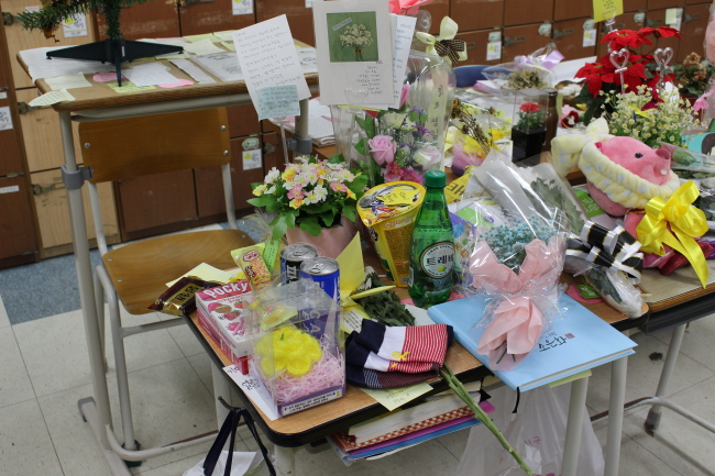 Gifts left by visitors are laid on the desk of Cho Eun-hwa, one of the four students of Danwon High School who remains missing. (Yoon Min-sik/The Korea Herald)