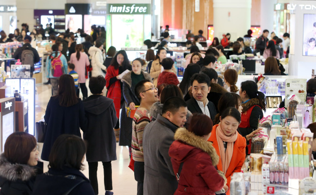 Customers cram a duty-free store located at Lotte World Tower in Jamsil, southeastern Seoul. (Yonhap)