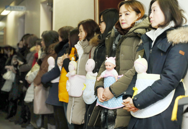 Members of an association of child care centers in Incheon City carry baby dolls as part of a demonstration to call for prompt execution of the Nuri budget by Incheon City and Incheon Metropolitan City Office of Education at Incheon City Hall on Wednesday. Yonhap