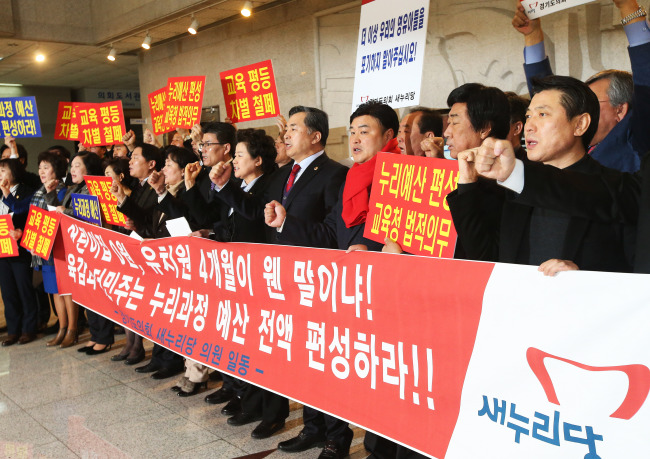 """Saenuri Party members of the Gyeonggi provincial assembly on Thursday demand the provincial government to allocate budgets for the free childcare """"Nuri"""" program in Suwon, Gyeonggi Province. / Yonhap"""