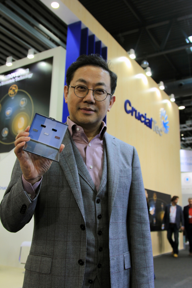 CrucialTec CEO Charles Ahn poses with fingerprint modules of the firm at the MWC trade show in Barcelona in March last year.(CrucialTec)