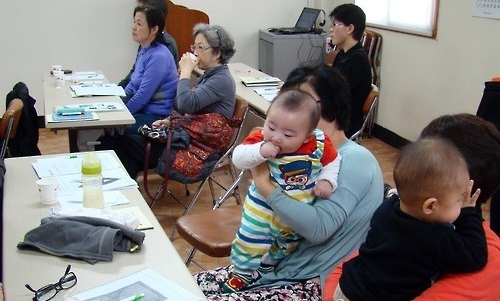 Participants listen to tips on taking care of babies during a class arranged by the Busan office of Korea Population, Health and Welfare Association for grandparents taking care of their grandchildren. (Yonhap)