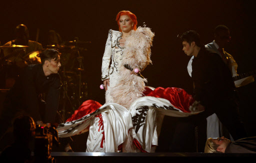 Lady gaga is aided with her costume as she performs a medley of david