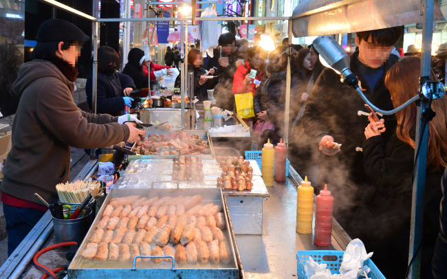 Myeong-dong bustles with carts offering various snacks. (Herald photo)