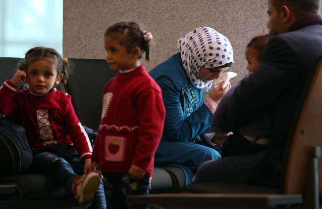 """A Syrian family seeking refuge in South Korea waits for authorities to begin the process at Incheon International Airport on Nov. 18, 2015. According to the National Intelligence Service, of the 200 Syrian asylum seekers who arrived in Korea, 135 have been recognized with """"humanitarian status,"""" while 65 are still waiting inside the airport as of the end of last year. (Yonhap)"""