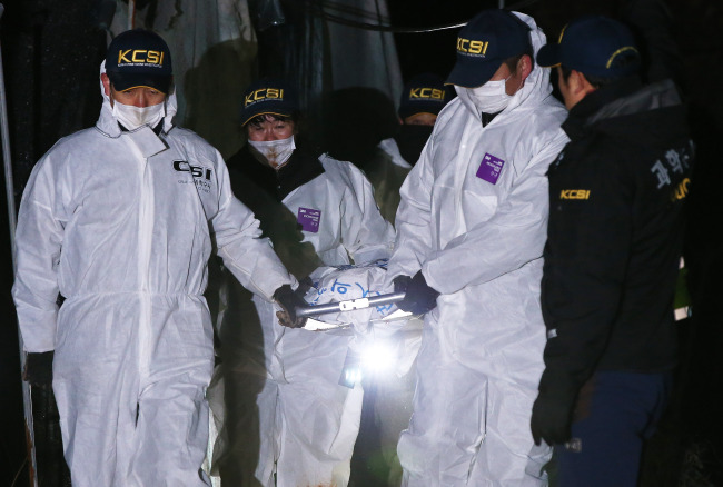 Police officers recover the body of a 7-year-old who was beaten to death by her 42-year-old mother and buried in a mountain in Gwangju, Gyeonggi Province, on Feb. 15. (Yonhap)