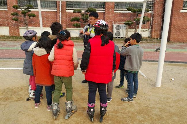 A police officer teaches children how to report child abuse cases at a school in Gwangju on Feb. 23. (Yonhap)