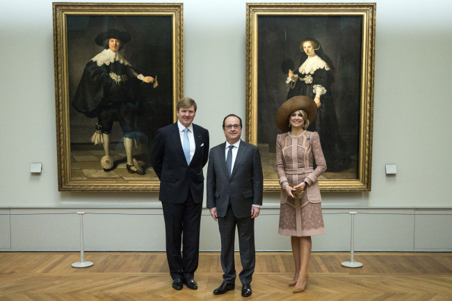 French President Francois Hollande (center), Netherlands' King Willem-Alexander (left) and Queen Maxima pose next to two of Rembrand's paintings, the portrait of Marten Soolmans (left), and the portrait of Oopjen Coppit. (AP-Yonhap)