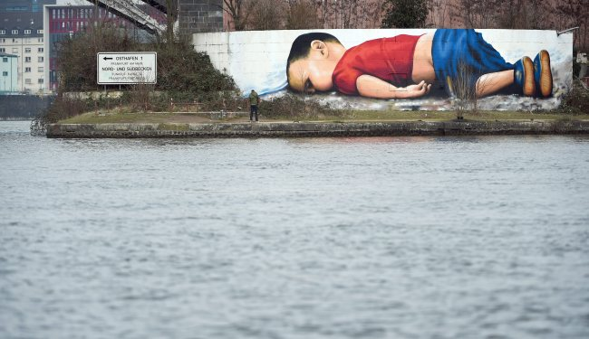 A huge graffiti artwork of Syrian toddler Aylan Kurdi, by Frankfurt artists Justus Becker and Oguz Sen is seen on a wall on the banks of river Main near the headquarters of the European Central Bank in Frankfurt, Germany, on March 10. (EPA-Yonhap)