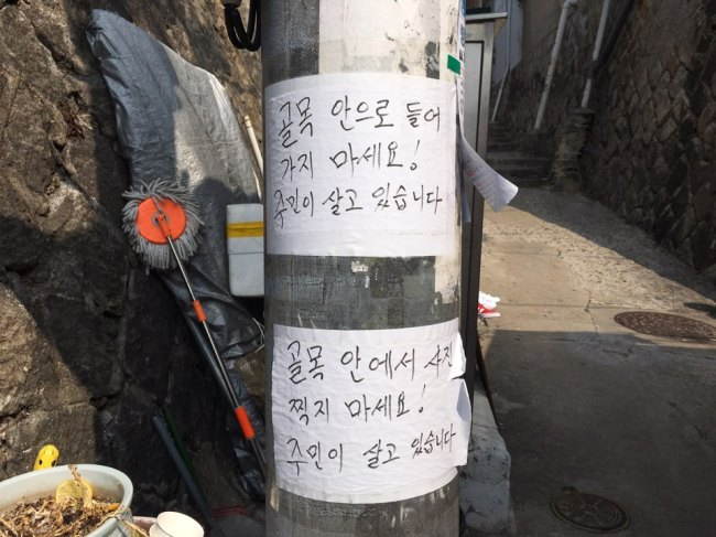 "Signs posted on a pole in Ihwa-dong read, ""Do not enter the alley,"" ""Do not take pictures inside the alley. There are people living here."" (Kim Da-sol/The Korea Herald)"