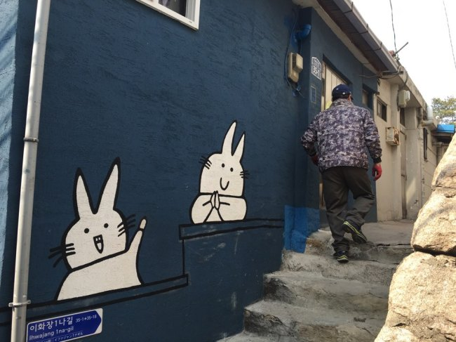 A resident walks into his home where the wall is painted with a mural in Ihwa-dong. (Kim Da-sol/The Korea Herald)