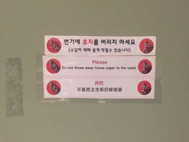 A public bathroom stall in Seoul has a sign that asks users not to flush waste paper down the toilet, and to discard them in trash cans instead, as water pressure is low. (Claire Lee/The Korea Herald)