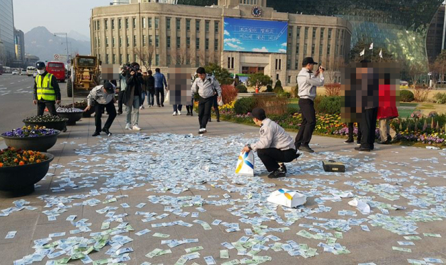 Police collect the banknotes scattered on the street in downtown Seoul on Monday. (Yonhap)