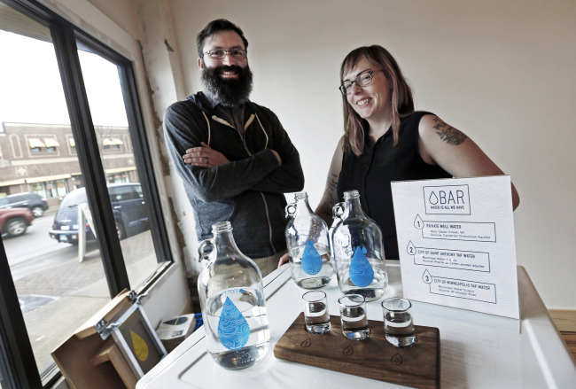 Colin Kloecker and his wife, Shanai Matteson, pose with water in growlers and glasses in the building where they are preparing to open a storefront Water Bar in northeast Minneapolis on March 16. (AP-Yonhap)
