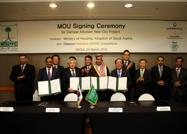 Hanwha E&C president Choi Kwang-ho (fifth from right), Daewoo E&C president Park Young-shik (fourth from left) and Saudi Housing Minister Majed al-Hogail (center) pose during a memorandum of understanding signing ceremony to build 100,000 homes in Saudi Arabia in a Seoul hotel on Thursday. Hanwha E&C New Growth Strategy Team Leader Kim Dong-sun (fourth from right), the third son of Hanwha Group chairman Kim Seung-youn, also attended the event. (Hanwha E&C)