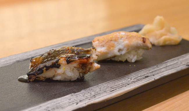 Sushi Matsumoto`s anago, salt-water eel, served as a pair, one adorned with a soy sauce-based lacquer (left) and the other with salt and yuzu. (Lee Sang-sub/The Korea Herald)