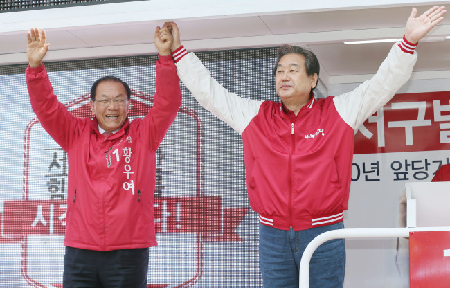 The ruling Saenuri Party chief Rep. Kim Moo-sung (right) cheers on Saturday for Rep. Hwang Woo-yea, candidate for Incheon's Seo-gu-B constituency. Yonhap
