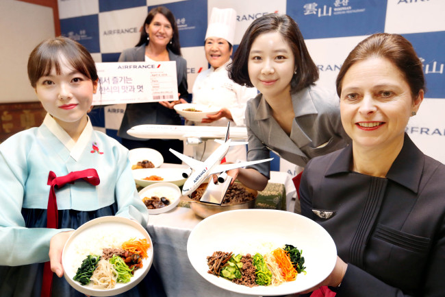 KOREAN FOOD IN THE AIR - Celine Balmelle, general manager of Air France-KLM in Korea (far right) and chef Kim Youn-young of Korean restaurant Woonsan (center), pose at Woonsan in Yeouido, Seoul on Monday, with the new in-flight Korean food menu to be offered on Air France's business class between Paris and Seoul. The new Korean menu includes bibimbap, bulgogi, steamed ribs and spicy stewed chicken. (Yonhap)