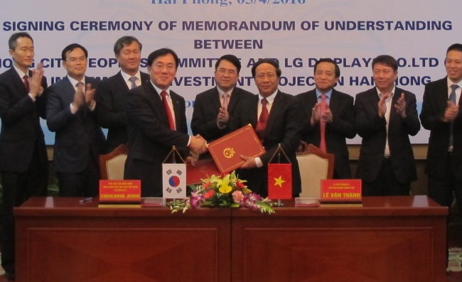 Jeong Cheol-dong (fourth from left), LG Display chief production officer, and Le Van Thanh (fourth from right), chief secretary of the Hai Phong city government, pose for photos at a MOU signing ceremony held in the city on Tuesday. (LG Display)