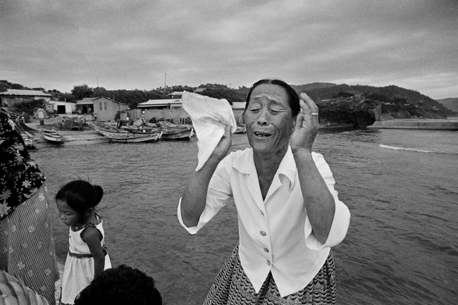 An elderly mother wails during a shamanic ritual to retrieve the soul of her son, who died during a sea storm, and send it on its way to heaven, in Pohang, North Gyeongsang Province, in 1981. (Photograph by Kim Soo-nam/The National Folk Museum of Korea)