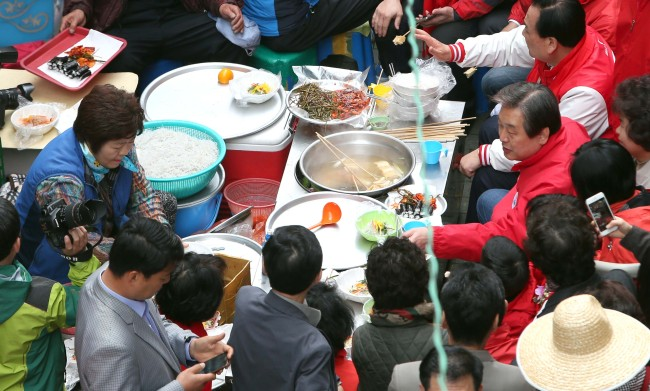 Saenuri Party chief Rep. Kim Moo-sung (center right) has lunch while campaigning in Junggu, Busan, Monday. (Yonhap)