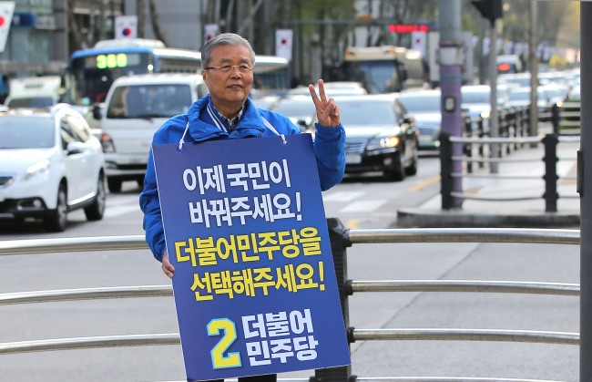 The Minjoo Party of Korea chief Kim Chong-in urges voters to cast their ballot wearing a picket on a street in Seonneung, southern Seoul, on Monday. (Yonhap)