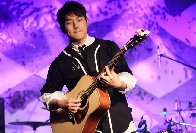 Singer-songwriter Sam Kim performs onstage in Itaewon on Monday. (Yonhap)