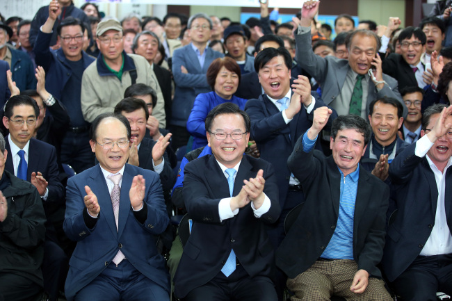 The Minjoo Party of Korea's Kim Boo-kyum (center) cheers with his supporters upon exit poll results that showed him holding a lead against rivals in his constituency at the conservative stronghold in Daegu on Wednesday. Yonhap