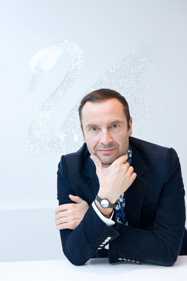 Robert Buchbauer, CEO of Consumer Goods Business of Swarovski, poses in front of the brand's iconic swan logo at a Swarovski store in Garosugil, Seoul, on Tuesday.(Jang Jong-hoon)