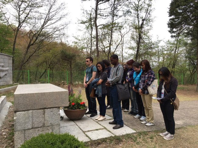 A group of foreign students pay tribute Monday in front of the tombstone of patriot Yi Jun at the April 19 National Cemetery. Kim Da-sol/The Korea Herald