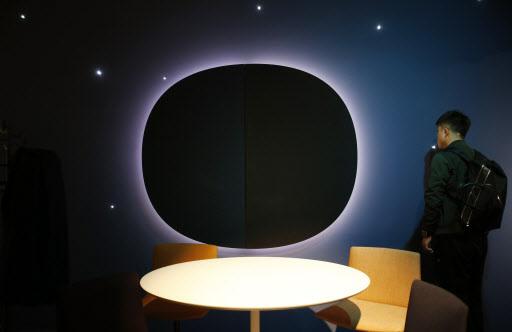A man views Arper`s furniture exposition, part of the design fair, in Milan, Italy. (AP-Yonhap)