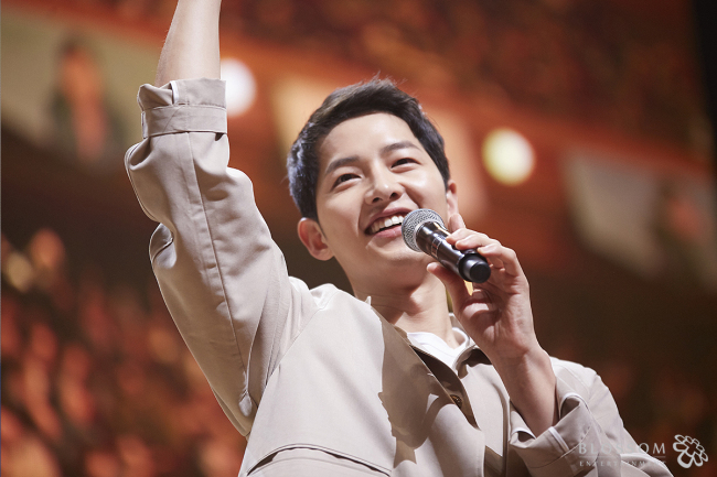 Song Joong-ki waves to the audience at a fan meeting in Seoul on April 18. (Blossom Entertainment)
