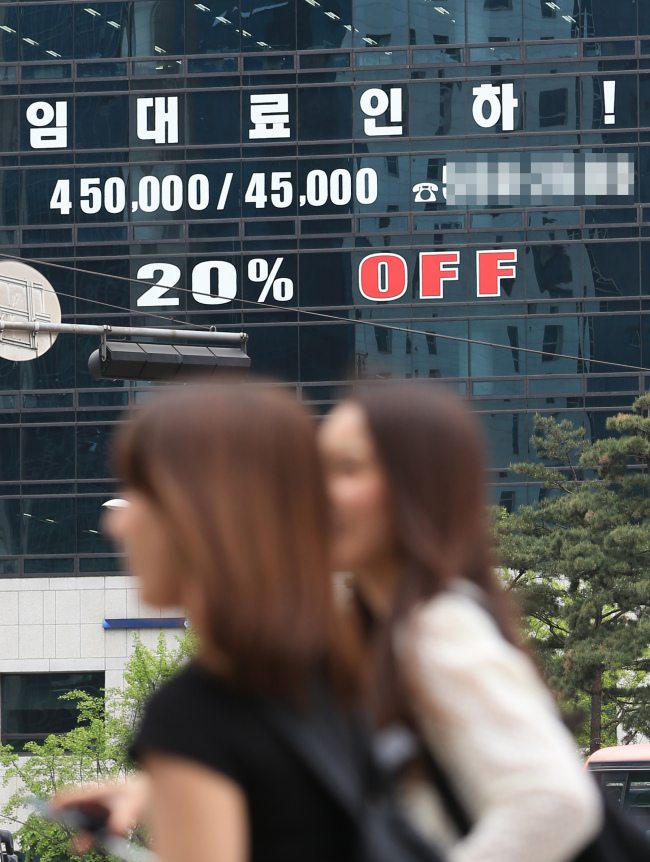 LEASE FEE DISCOUNT -- Two women walk past a building in Gangnam, southern Seoul, which is publicizing a 20 percent discount on the rental fees of offices, on Wednesday. The government said the average vacant ratio of office buildings in Seoul soared to 10.1 percent in the first quarter of this year due to the increased supply of offices and the protracted, sluggish real estate market. (Yonhap)