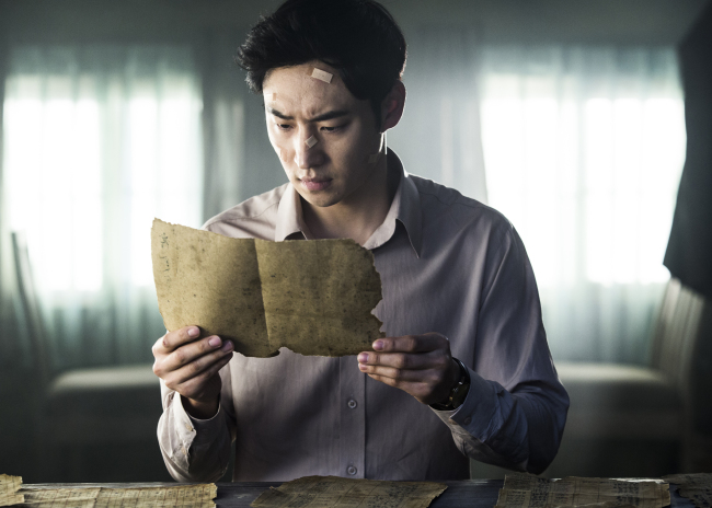 """Hong Gil-dong, played by Lee Je-hoon, discovers a document in """"Phantom Detective."""" (CJ E&M)"""