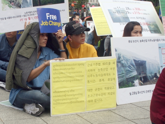 Migrant workers listen to speakers at a May Day rally in front of the Bosingak Bell in central Seoul on Sunday. (Paul Kerry/The Korea Herald)