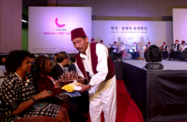 An Algerian man offers dates -- a dried, fleshy fruit popular in the Middle East and North Africa -- to participants. (Joel Lee / The Korea Herald)