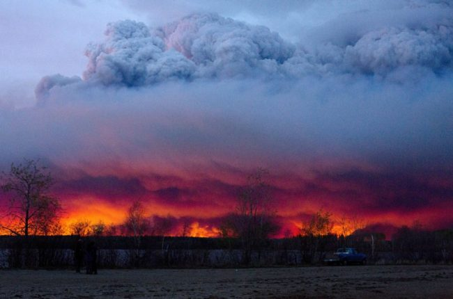 A wildfire moves toward the town of Anzac on Wednesday, where was set up as an evacuation center for those ordered to leave Fort McMurray. (AP)