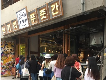Customers wait in line to eat at YG Entertainment's Hongdae barbecue restaurant Samgeori Pujutgan. (YG Entertainment)